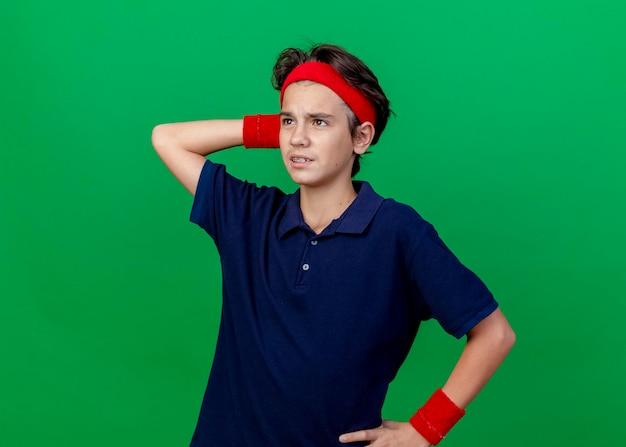 Verwirrter junger hübscher sportlicher junge, der stirnband und armbänder mit zahnspangen trägt, die hand auf taille und hinter kopf halten, die gerade lokal auf grüner wand mit kopienraum suchen
