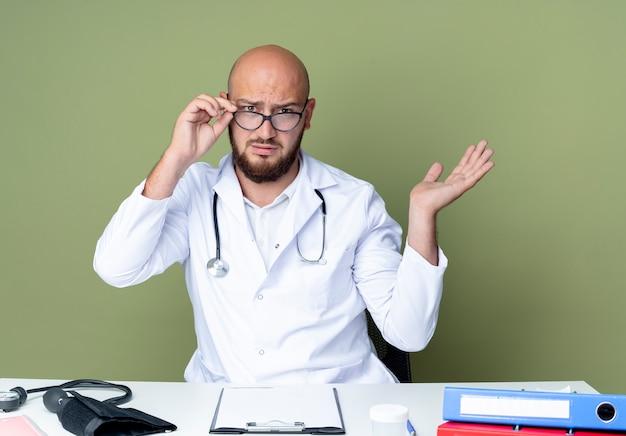 Verwirrter junger kahlköpfiger männlicher arzt, der medizinische robe und stethoskop trägt, die an schreibtischarbeit mit medizinischen werkzeugen sitzen, nehmen brille auf und verbreiten hand lokalisiert auf grünem hintergrund
