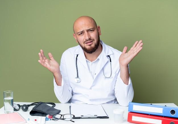 Verwirrter junger kahlköpfiger männlicher arzt, der medizinisches gewand und stethoskop trägt, der am schreibtisch sitzt