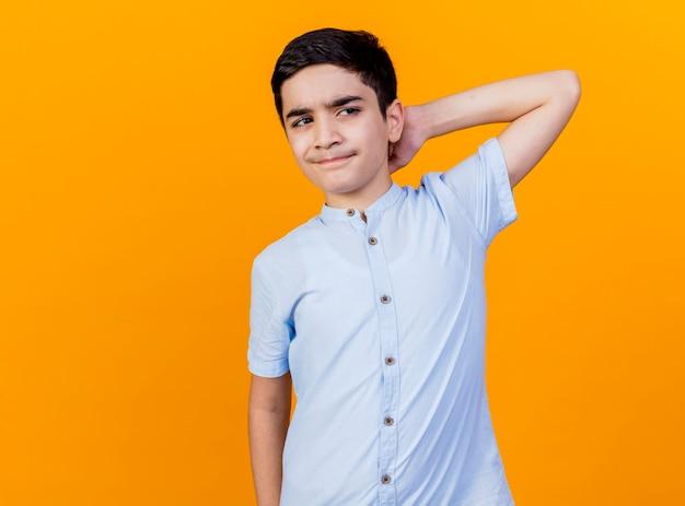 Verwirrter junger kaukasischer junge, der seite betrachtet, die hand hinter hals lokalisiert auf orange hintergrund mit kopienraum hält