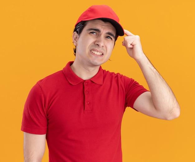 Verwirrter junger kaukasischer lieferbote in blauer uniform und mütze, der nach oben schaut und denkgeste macht