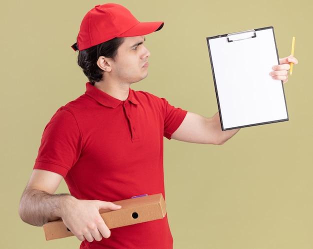 Verwirrter junger kaukasischer lieferbote in blauer uniform und mütze, der pizzapaket und zwischenablage mit bleistift hält, der auf zwischenablage schaut