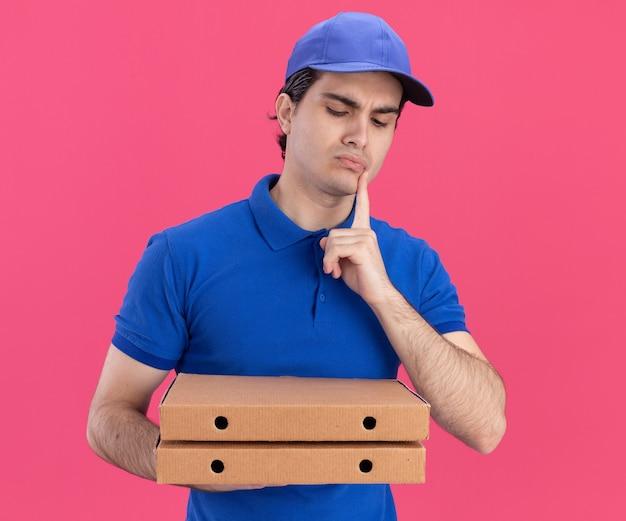 Verwirrter junger kaukasischer lieferbote in blauer uniform und mütze, die pizzapakete hält und betrachtet, die finger auf das kinn legen