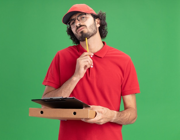 Verwirrter junger kaukasischer lieferbote in roter uniform und mütze mit brille, die pizzapaket-klemmbrett hält und das kinn mit bleistift berührt