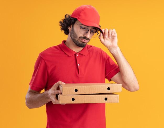Verwirrter junger kaukasischer lieferbote in roter uniform und mütze mit brille, die pizzapakete hält und betrachtet, die mütze greifen