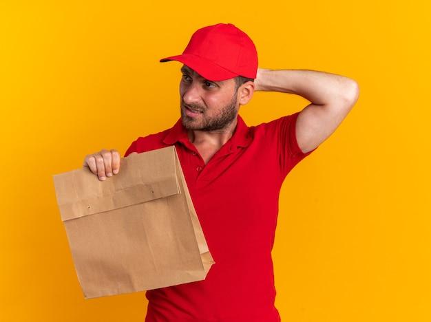 Verwirrter junger kaukasischer liefermann in roter uniform und mütze mit papierpaket, der die hand hinter dem kopf hält und auf die seite isoliert auf der orangefarbenen wand schaut