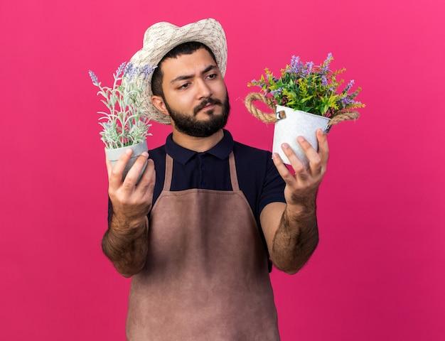 Verwirrter junger kaukasischer männlicher gärtner mit gartenhut, der blumentöpfe isoliert auf rosa wand mit kopienraum hält