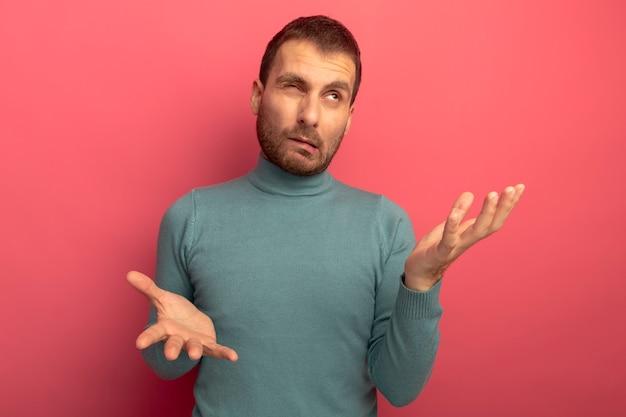 Verwirrter junger kaukasischer mann, der nach oben schaut und leere hände mit einem geschlossenen auge lokal auf purpurroter wand zeigt