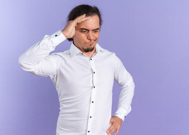 Verwirrter junger kaukasischer mann im weißen hemd, der sich die hand auf die stirn legt und nach unten schaut