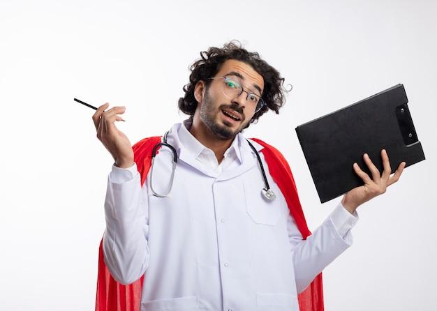 Verwirrter junger kaukasischer superheldenmann in der optischen brille, die arztuniform mit rotem umhang und mit stethoskop um hals hält, das bleistift und klemmbrett lokalisiert auf weißer wand hält