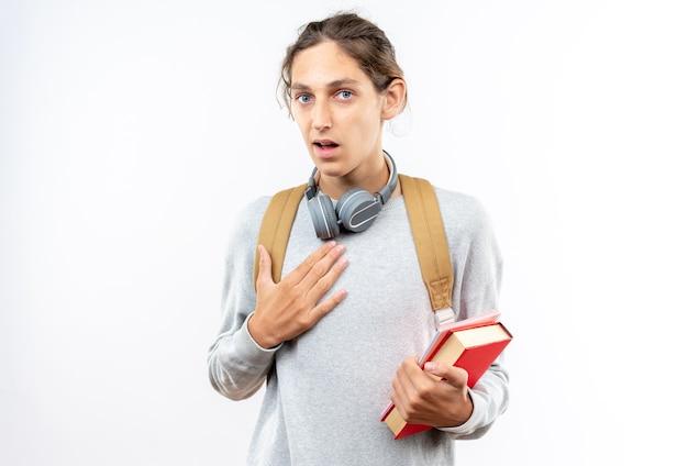 Verwirrter junger kerl, der einen rucksack mit kopfhörern am hals trägt und bücher hält, die hand auf das herz legen, isoliert auf weißer wand