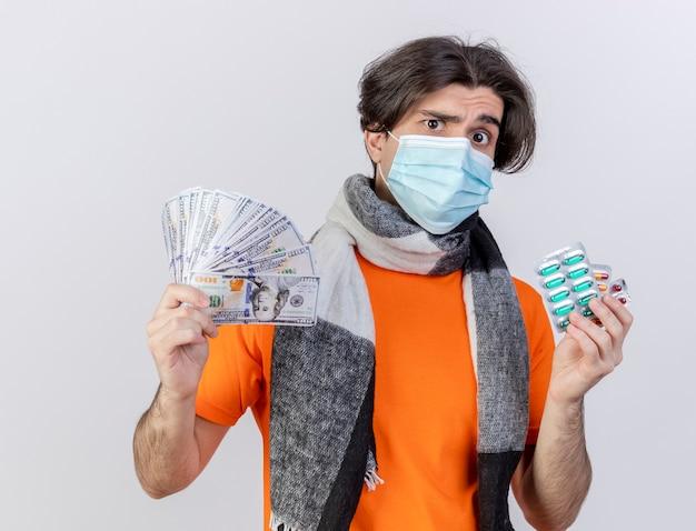 Verwirrter junger kranker mann, der schal und medizinische maske hält, die bargeld mit pillen lokalisiert auf weißem hintergrund hält