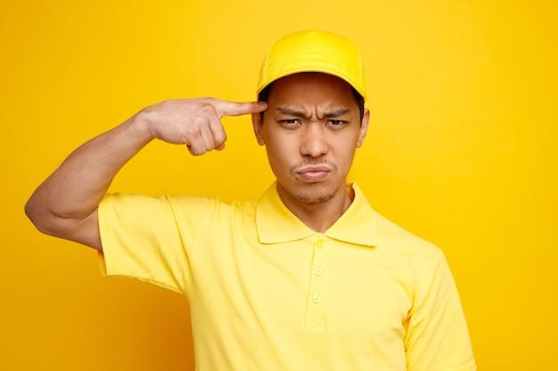 Verwirrter junger lieferbote, der mütze und uniform trägt und denkgeste tut