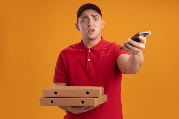 Verwirrter junger lieferbote, der uniform mit kappe hält, die pizzaschachteln hält und telefon an der front lokalisiert auf orange wand hält