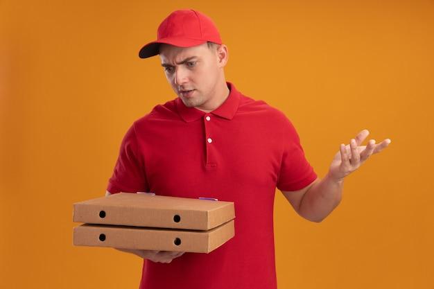 Verwirrter junger lieferbote, der uniform mit kappe hält und pizzakästen betrachtet, die hand lokalisiert auf orange wand verbreiten