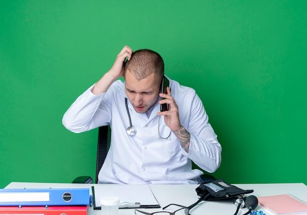 Verwirrter junger männlicher arzt, der medizinische robe und stethoskop trägt, sitzt am schreibtisch mit arbeitswerkzeugen, die am telefon mit der hand auf dem kopf und den geschlossenen augen lokalisiert auf grün sprechen