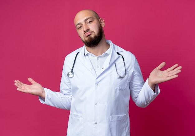 Verwirrter junger männlicher arzt, der medizinische robe und stethoskop trägt, spreizt hände