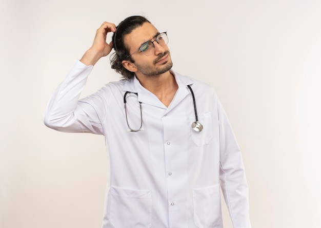 Verwirrter junger männlicher arzt mit optischer brille, die weiße robe mit stethoskop trägt, das hand auf kopf setzt