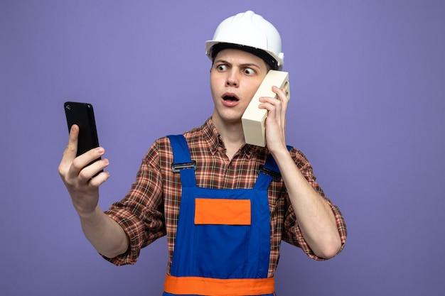 Verwirrter junger männlicher baumeister, der uniform mit telefon trägt, spricht auf ziegelstein