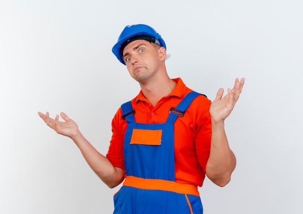 Verwirrter junger männlicher baumeister, der uniform und schutzhelm trägt, breitet hände aus