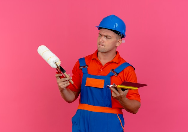 Verwirrter junger männlicher baumeister, der uniform- und schutzhelm trägt, der bauwerkzeuge hält und betrachtet