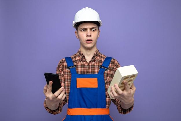 Verwirrter junger männlicher baumeister in uniform, der das telefon mit ziegelstein hält und betrachtet