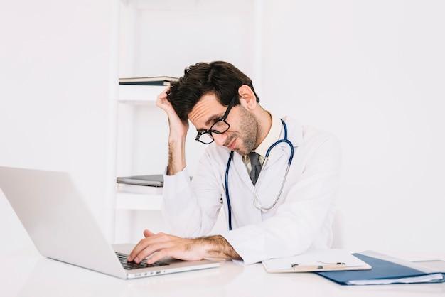 Verwirrter junger männlicher doktor, der laptop verwendet