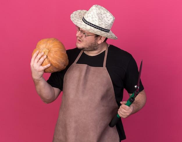 Verwirrter junger männlicher gärtner, der gartenhut trägt, der haarschneidemaschinen hält und kürbis in seiner hand lokalisiert auf rosa wand betrachtet