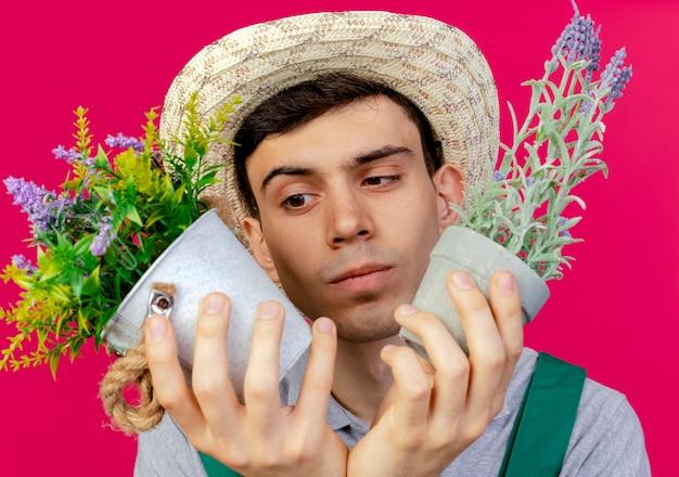 Verwirrter junger männlicher gärtner, der gartenhut trägt, hält und schaut auf blumentöpfe