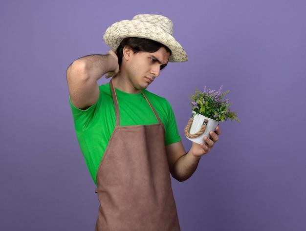 Verwirrter junger männlicher gärtner in der uniform, die gartenhut hält und blume im blumentopf betrachtet und hand auf hals lokalisiert auf purpur betrachtet