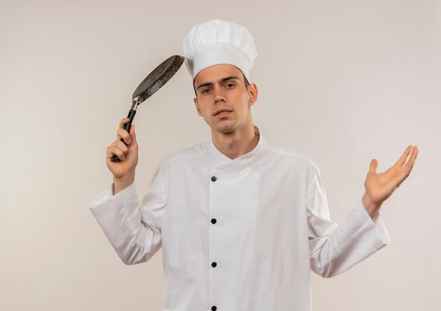 Verwirrter junger männlicher koch, der kochuniform trägt, die bratpfanne um kopf spreizt hand auf isolierter weißer wand mit kopienraum ausbreitet