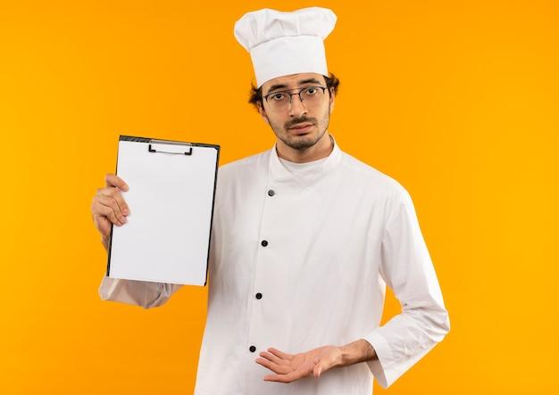 Verwirrter junger männlicher koch, der kochuniform und brille hält, die klemmbrett hält
