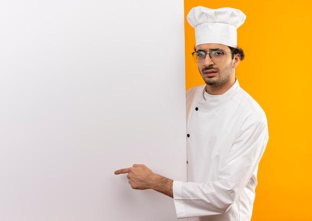 Verwirrter junger männlicher koch, der kochuniform und brille hält und auf weiße wand zeigt