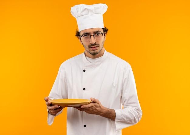 Verwirrter junger männlicher koch, der kochuniform und brillenteller trägt
