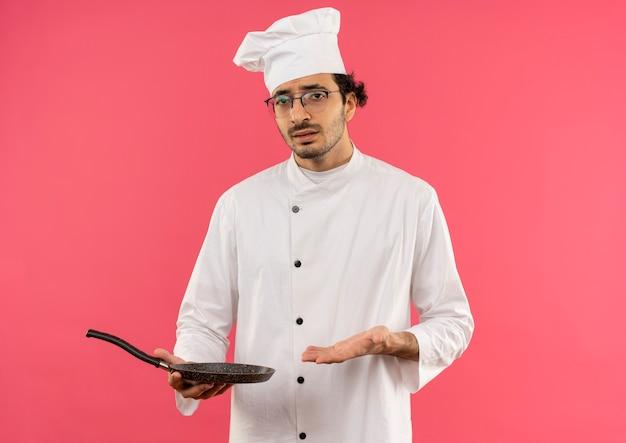 Verwirrter junger männlicher koch, der kochuniform und gläser hält und mit der hand auf bratpfanne zeigt