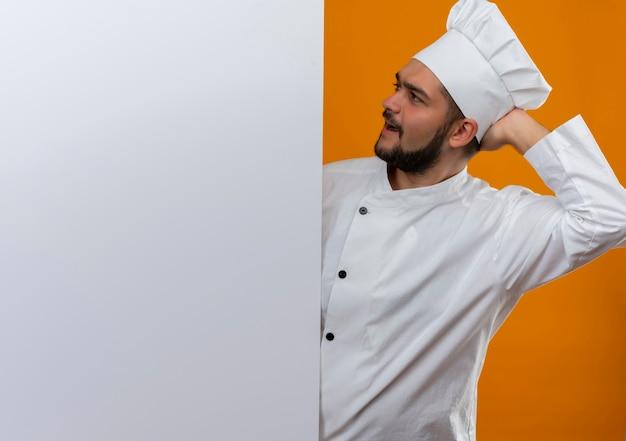Verwirrter junger männlicher koch in kochuniform, der dahinter steht und die weiße wand mit der hand hinter dem kopf einzeln an der orangefarbenen wand mit kopienraum betrachtet
