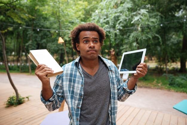 Verwirrter junger mann, der buch und tablette im freien hält