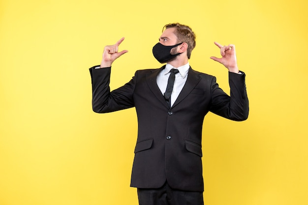 Verwirrter junger mann, der die finger auf beide seiten zeigt und nicht sicher ist, welche wahl er auf gelb treffen soll