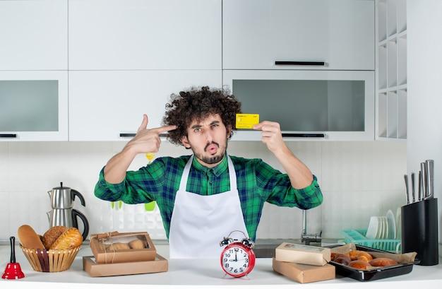 Verwirrter junger mann, der hinter dem tisch verschiedenes gebäck darauf steht und bankkarte in der weißen küche zeigt