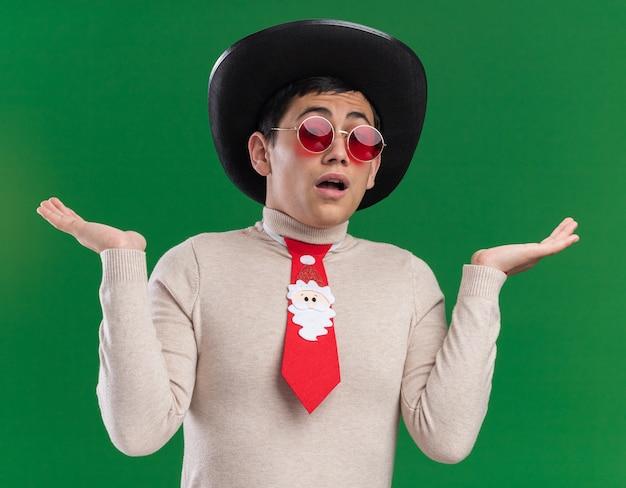 Verwirrter junger mann, der hut mit weihnachtskrawatte und brille trägt, die hände lokalisiert auf grünem hintergrund verbreiten