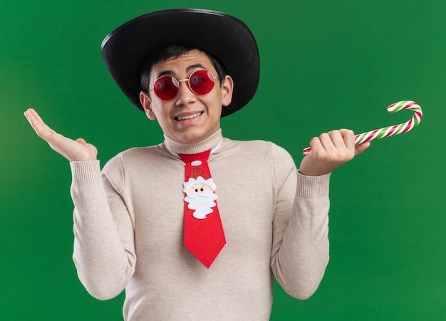 Verwirrter junger mann, der hut mit weihnachtskrawatte und gläsern hält, die weihnachtsbonbons verbreiten, die hände lokalisiert auf grüner wand verteilen