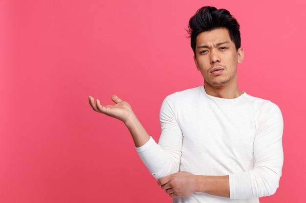 Verwirrter junger mann, der leere hand zeigt