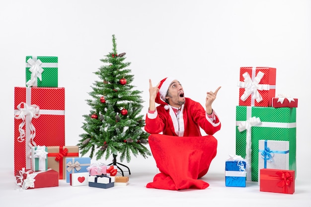 Verwirrter junger mann verkleidet als weihnachtsmann mit geschenken und geschmücktem weihnachtsbaum, der auf dem boden sitzt und oben auf weißem hintergrund schaut