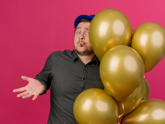Verwirrter junger party-typ, der blauen hut trägt, der nahe luftballons steht, die partygebläse im mund halten, der auf rosa isolierte hände spreizt