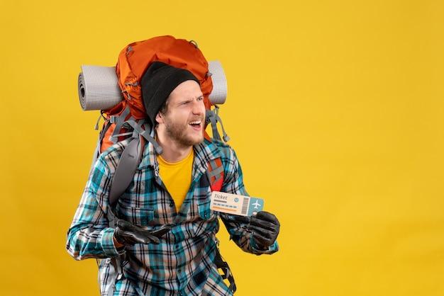 Verwirrter junger rucksacktourist mit schwarzem hut, der flugticket hält