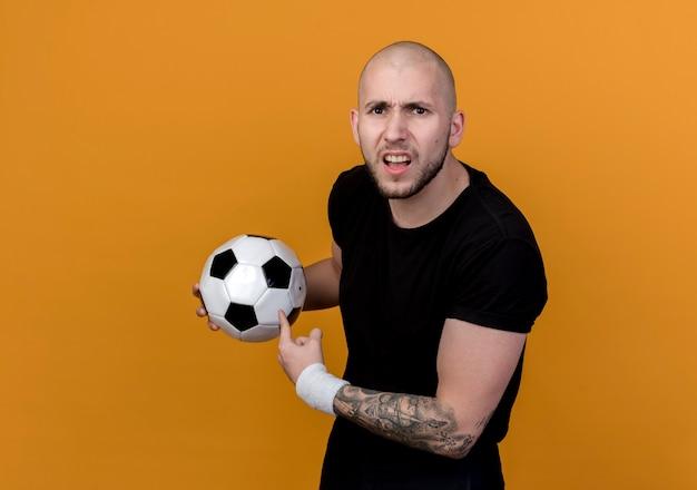 Verwirrter junger sportlicher mann, der armband hält und punkte auf kugel lokalisiert auf orange hintergrund trägt