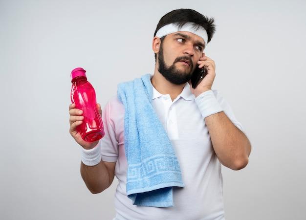 Verwirrter junger sportlicher mann, der stirnband und armband mit handtuch auf schulter hält, die wasserflasche hält, spricht am telefon lokalisiert auf weißer wand