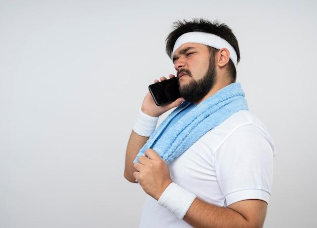 Verwirrter junger sportlicher mann, der stirnband und armband mit handtuch auf schulter trägt, spricht am telefon lokalisiert auf weißer wand mit kopienraum