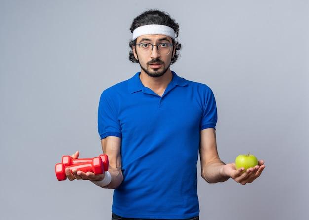 Verwirrter junger sportlicher mann mit stirnband mit armband, das hanteln mit apfel hält