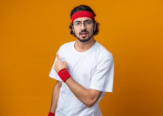 Verwirrter junger sportlicher mann mit stirnband mit armbandpunkten an der seite